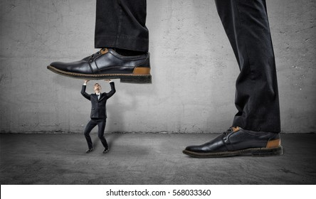Little frightened worker under a feet of a huge businessman on grey wall background. Chiefs pressure. Stress on work. Business ranking.