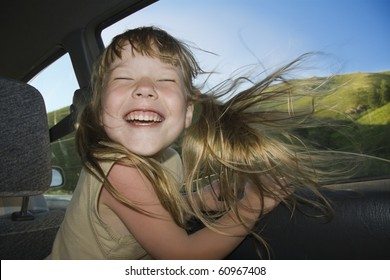 Little fun girl speeds in car near the open window.