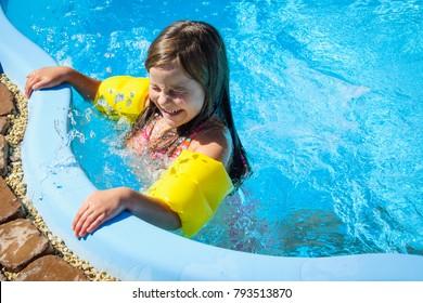 Little fun girl is in swimming pool