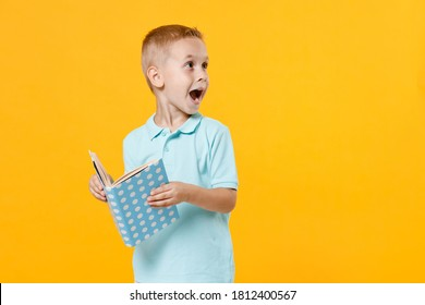 Little fun male fair-haired brown-eyed kid boy 5-6 years old wearing stylish blue turquoise t-shirt polo holding in hands reading book isolated on yellow color wall background, child studio portrait