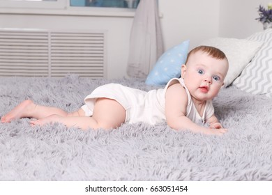 Little funny baby in white lies on bed with pillows in bedroom