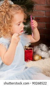 little funny blonde girl with lipstick near Christmas tree