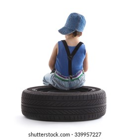 little funny boy with car wheel on white background