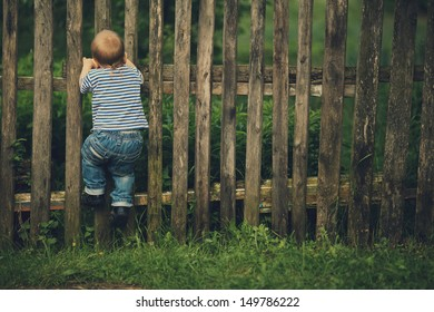 little funny boy with fence outdoors