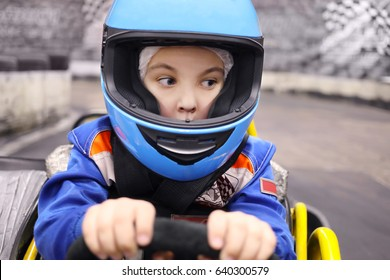 Little funny boy in helmet drives in go-kart on track during competition