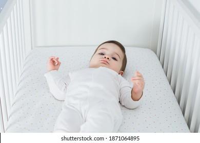 Kleiner lustiger Junge, der im Babybett liegt. Lächelt ein liebenswertes Kind auf seinem Schoß im Krimi. Kinderporträt in der Kindergarten. Happy-Kindheit-Konzept - Draufsicht