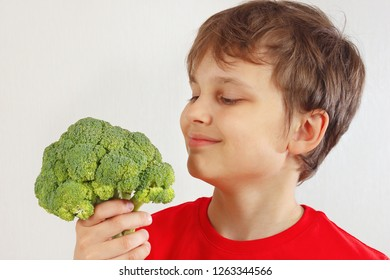 Little funny boy in a red shirt with broccoli on a white background