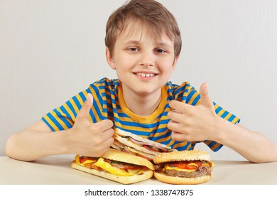 Little funny boy in a striped shirt at the table recommends hamburgers and sandwich on a white background