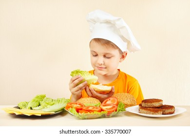 Little funny chef puts lettuce on the sandwich
