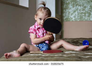 Little Funny Curious Baby Girl withTable Tennis racket at home