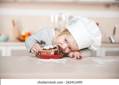 Little funny girl with chef hat eating cake and looking at camera. Kitchen interior. Concept for young kitchen hands
