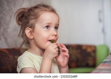 Little funny girl eats marmalade closeup portrait