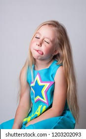 little funny girl ina blue jumpsuite with a colorful staron it showing tongue and playing with audience