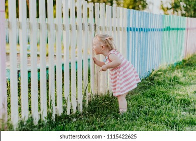 A little funny girl looks through the fence to the playground