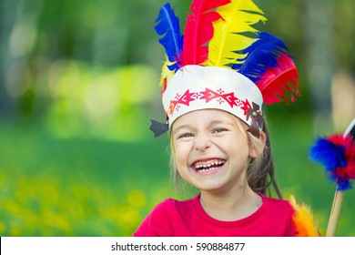 little funny girl playing native american in summer park
