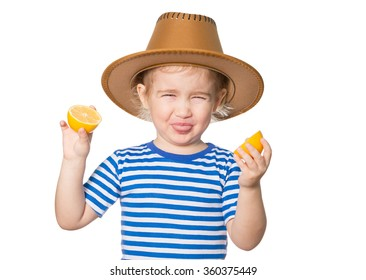 Little Funny girl in striped shirt and hat keeps lemons. Isolated on white background