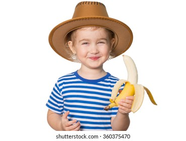 Little Funny girl in striped shirt and hat eats banana. Isolated on white background