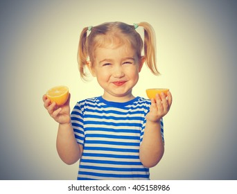 Little Funny girl in striped shirt  keeps lemons. Isolated on gray background