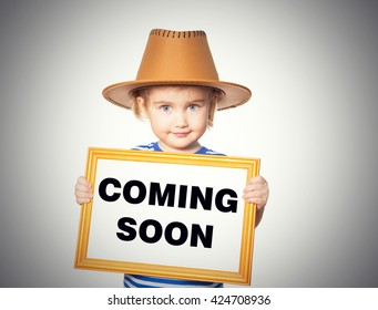 Little Funny girl in striped shirt with blackboard. Text  coming soon.  Isolated on gray background.