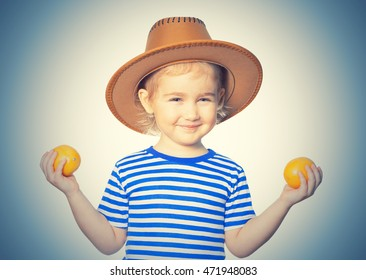 Little Funny girl in striped shirt and hat keeps lemons. Isolated on  background