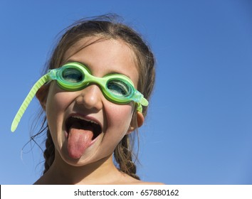Little funny girl with two pigtails and underwater glasses draw faces, shows tongue against the blue sky on the beach. Portrait of a small cheerful person.