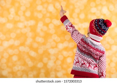 Little funny girl wearing Christmas clothes facing away and pointing with her finger on the yellow bright bokeh backdrop. Christmas concept.