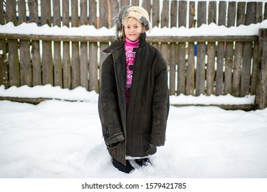 Little funny girl wearing oversized clothes and posing for camera in winter snowy day.