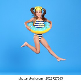 Little funny happy girl in swimsuit and goggles on her head jumping up in air with inflatable ring around waist, isolated over blue studio background. Summertime, vacation an school holidays concept