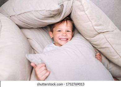 Little funny kid built impromptu fort house of pillows and blankets on bed.