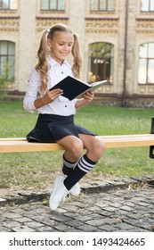 Little genius. Schoolgirl relaxing sit bench with book. Time to study. Studying in school yard. Student adorable child in formal uniform relaxing outdoors. Smart schoolgirl. Schoolgirl reading book.