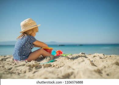 Little gilr playing on sandy beach with toys, holiday background