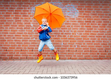 a little gilr with a umbrella  in front of a wall with a sketch a rain cloud