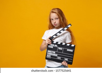 Little ginger kid girl 12-13 years old in white t-shirt isolated on yellow background children portrait. Childhood lifestyle concept. Mock up copy space. Hold classic black film making clapperboard