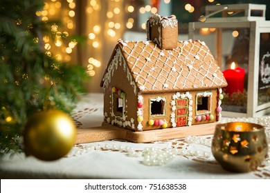 Little gingerbread house with glaze standing on table with tablecloth and decorations, candles and lanterns. Living room with lights and Christmas tree. Holiday mood