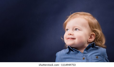 Little girl 2 - 3 years old wearing jeans shirt on a dark blue background