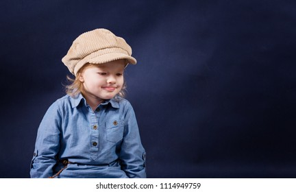 Little girl 2 - 3 years old wearing jeans shirt and funny hat on a dark blue background