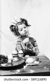 little girl 2 - 4 years in a red dress draws intently the pictures on the eggs with watercolors . at the head of the child ears of a rabbit preparing for Easter . monochrome , black and white