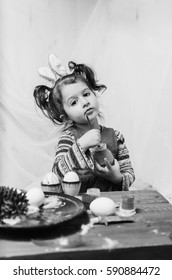 little girl 2 - 4 years in a red dress draws intently the pictures on the eggs with watercolors . at the head of the child ears of a rabbit preparing for Easter black and white , monochrome