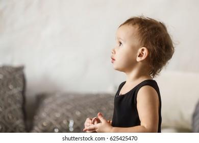 Little girl 2 year old wearing stylish black dress. Birthday in studio.
