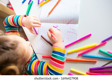 Little girl, a 3 year old girl, with a ponytail hairstyle in a multi-colored colorful striped jacket on a light background at the table draws multicolored markers and smiles