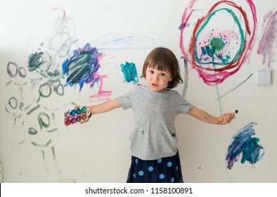 A little girl, 3 years old, painted an arched look with paint and a brush on the wall of her room. Naughty child, messing around