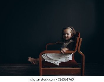 A little girl 3 years old is sitting in a retro chair on a dark background.