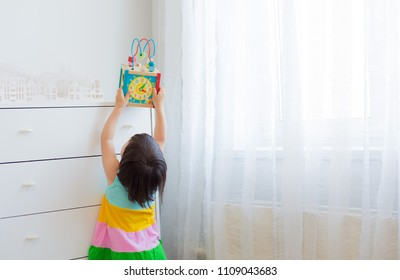 A little girl 3 years stretches to get an educational toy from a high shelf. Bright dress on the white background of the room. Free space. Out of reach of children, child safety