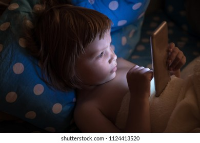 Little girl (3-4 years old) lies in bed in a dark room and looks at the smartphone screen. The child watching cartoons, playing games before a dream.