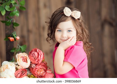 little girl 4 (fo?) years old with brown wavy hair and bow sits on a wooden ladder with Becket beautiful peony flowers and smiling with his hand propping up his head