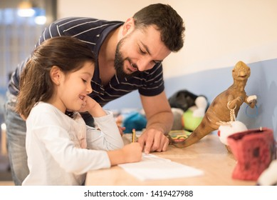 Little girl 6 years old doing homework at home in her room with her father