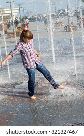 little girl 8 years in wet jeans and shirt playing in the fountain in the summer park