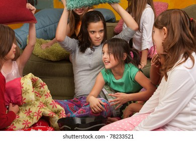 Little girl about to get whacked with a pillow at a sleepover