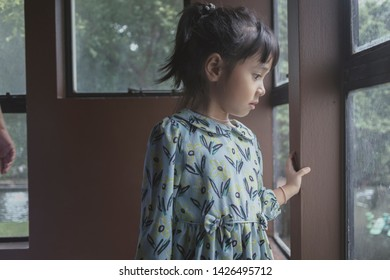 little girl absent minded looking outside