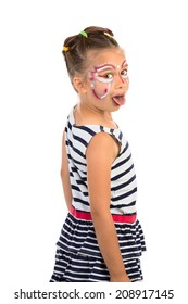 Little girl with an abstract paint on her face looking over her shoulder and showing her tongue, isolated